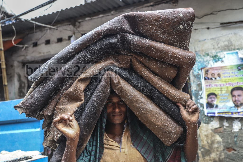A worker carrying rawhides after applying salt out of a warehouse in Dhaka's Posta. These will be transported to tanneries. Photo: Abdullah Al Momin