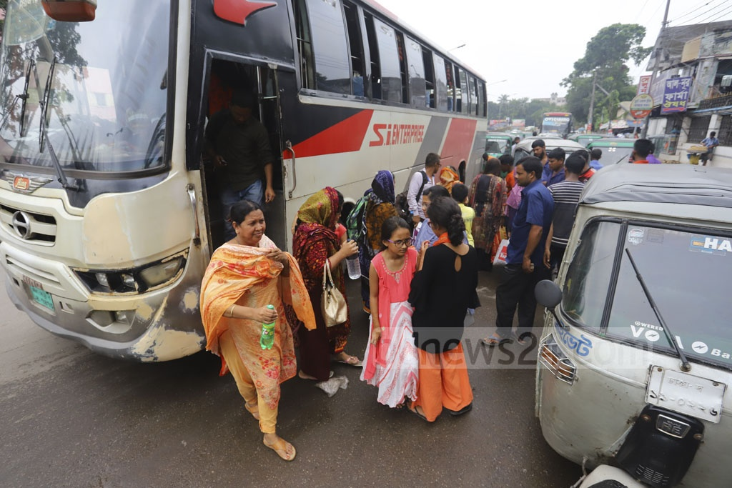 Passengers who have returned to Dhaka after celebrating Eid-ul-Azha with their families and relatives back home getting off buses in Shyamoli Technical area on Friday. Photo: Asif Mahmud Ove