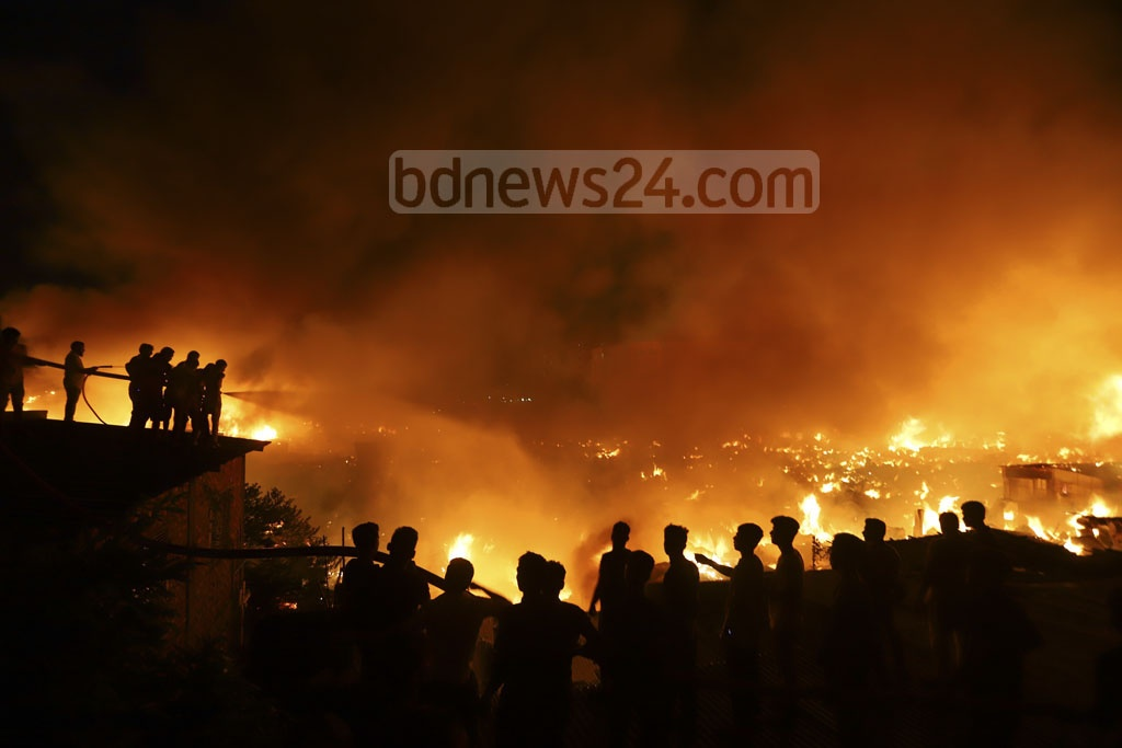 Slum dwellers join members of the Fire Service and Civil Defence in their efforts to put out a fire that destroyed hundreds of shanties at Mirpur in Dhaka on Friday. Photo: Asif Mahmud Ove