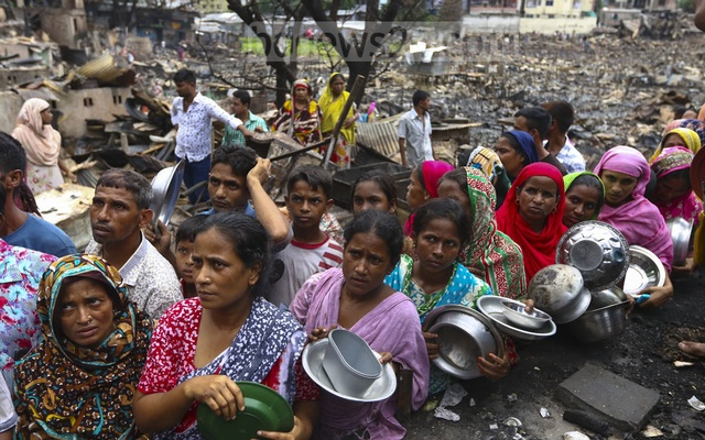 File Photo: Residents of Chalantika slum in Dhaka's Mirpur, now homeless after a devastating fire on Friday, waiting in queues for food being distributed by local public representatives on Sunday. Photo: Mahmud Zaman Ovi
