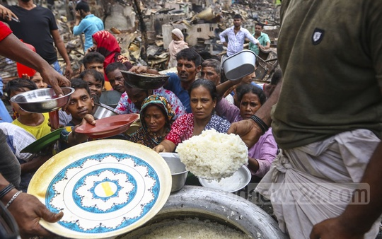 Residents of Chalantika slum in Dhaka's Mirpur, now homeless after a devastating fire on Friday, receiving food being distributed by local public representatives on Sunday. Photo: Mahmud Zaman Ovi