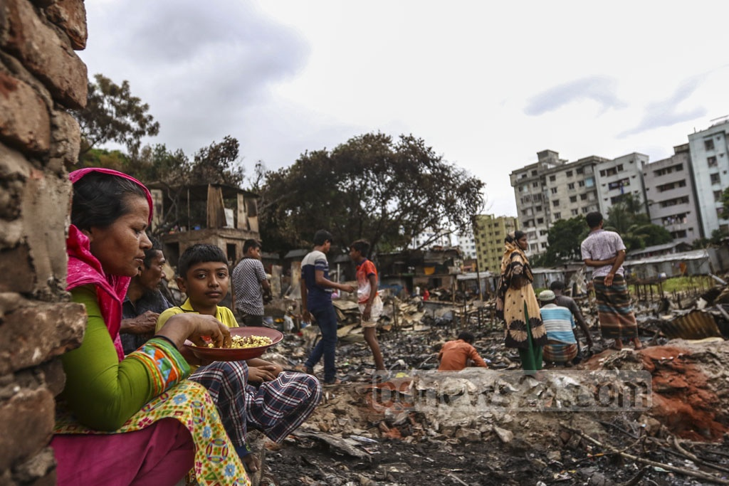 Phul Banu, who has been a resident of Chalantika slum in Dhaka's Mirpur for over three decades, eating under the open sky on Sunday after a fire destroyed her shanty along with hundred others on Friday. Photo: Mahmud Zaman Ovi