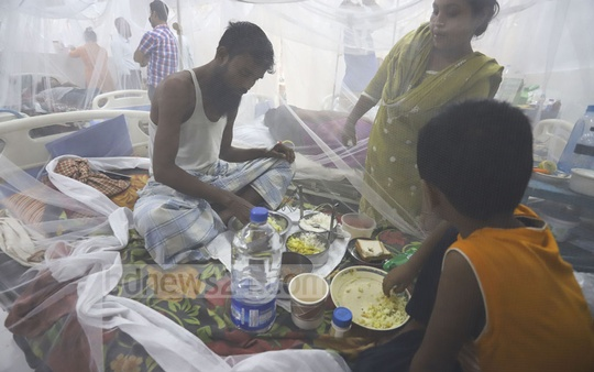 A dengue patient, 'Majid', eating food with his son Asaduzzaman inside a mosquito net at the Shaheed Suhrawardy Medical College Hospital in Dhaka on Sunday. He has been receiving treatment at the government facility for five days. Photo: Asif Mahmud Ove