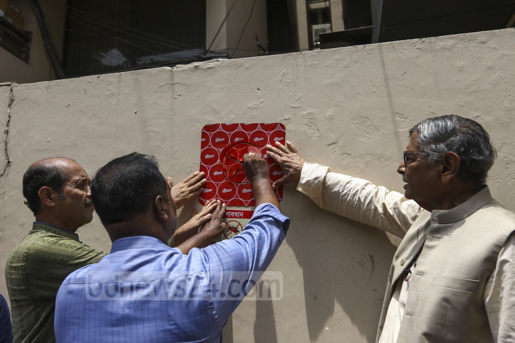 The Dhaka North City Corporation officials put a sticker after discovering Aedes larvae in a house at Gulshan. The authorities will fine the homeowner if they find the larvae upon their second visit in a week. Photo: Mahmud Zaman Ovi