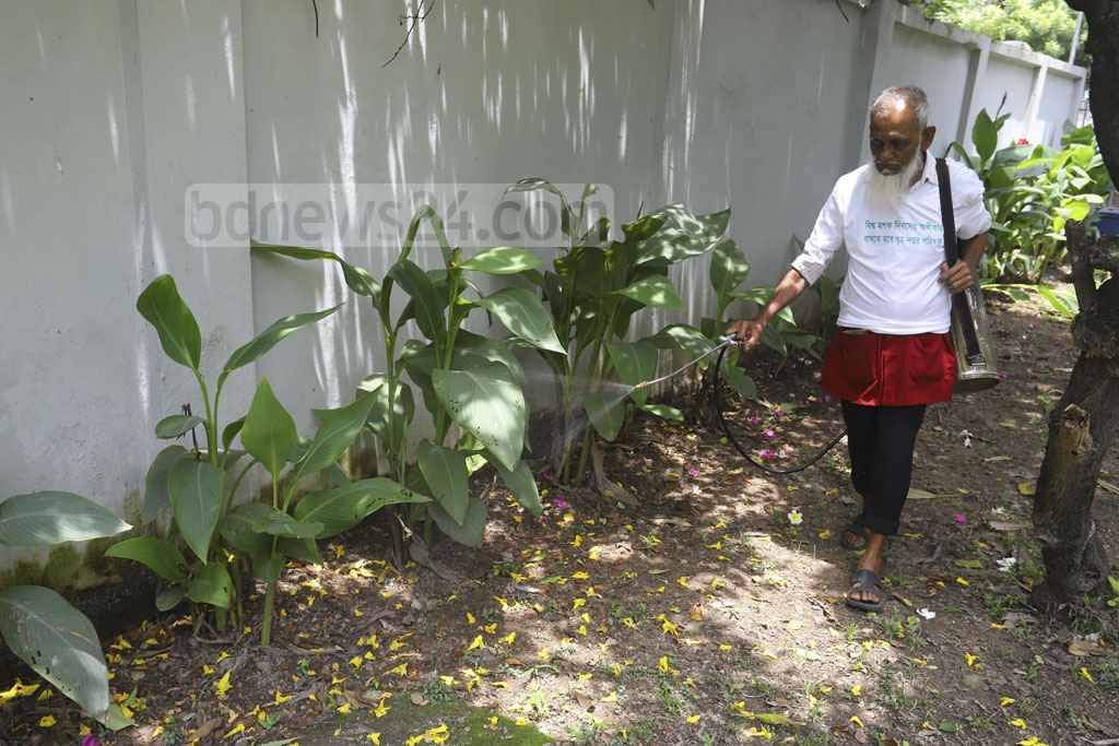 A cleaner sprays insecticide to exterminate the dengue-carrying Aedes mosquitoes at Dhaka Medical College Hospital on Tuesday. Photo: Asif Mahmud Ove
