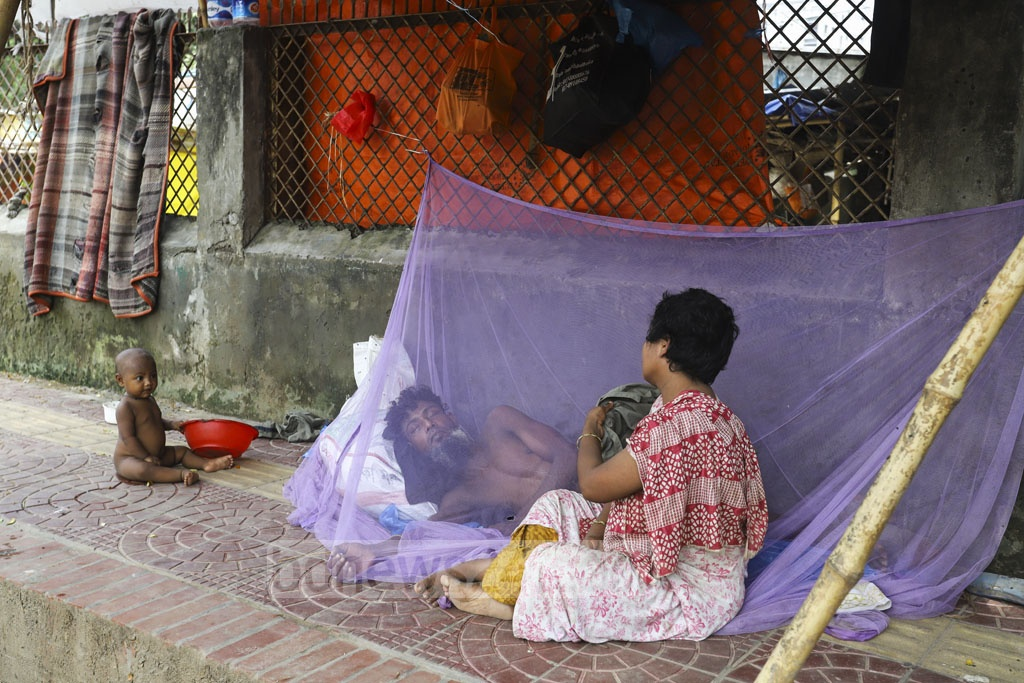 A member of a homeless family using a mosquito net even in daytime on a playground at Shahjahanpur Railway Colony in Dhaka to save himself from mosquito bite amid a dengue outbreak across Bangladesh. Photo: Asif Mahmud Ove