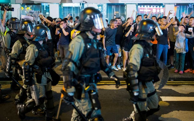 FILE PHOTO: Locals shout at riot police as they chase anti-government protesters down Nathan Road in Mong Kok in Hong Kong, China Aug 17, 2019. REUTERS