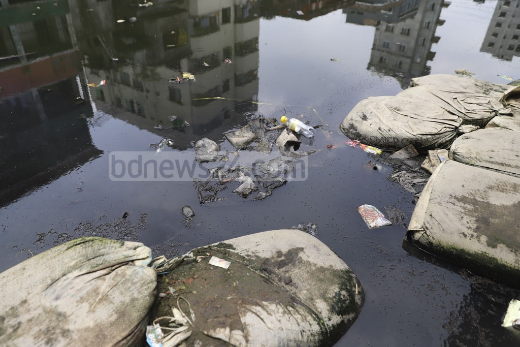 Mosquitoes just next to the students are spotted on the stagnant water in front of the Muradpur Adarsha High School in Dhaka. Photo: Abdullah Al Momin