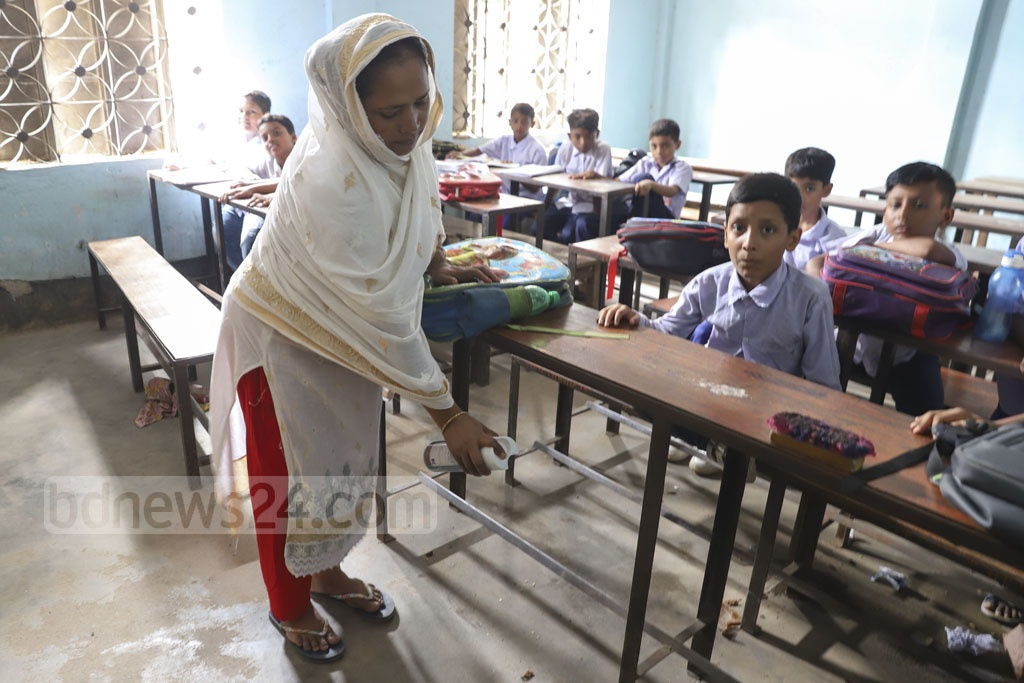 Mosquito repellents are being sprayed in the Muradpur Adarsha High School's classroom in Dhaka. Photo: Abdullah Al Momin