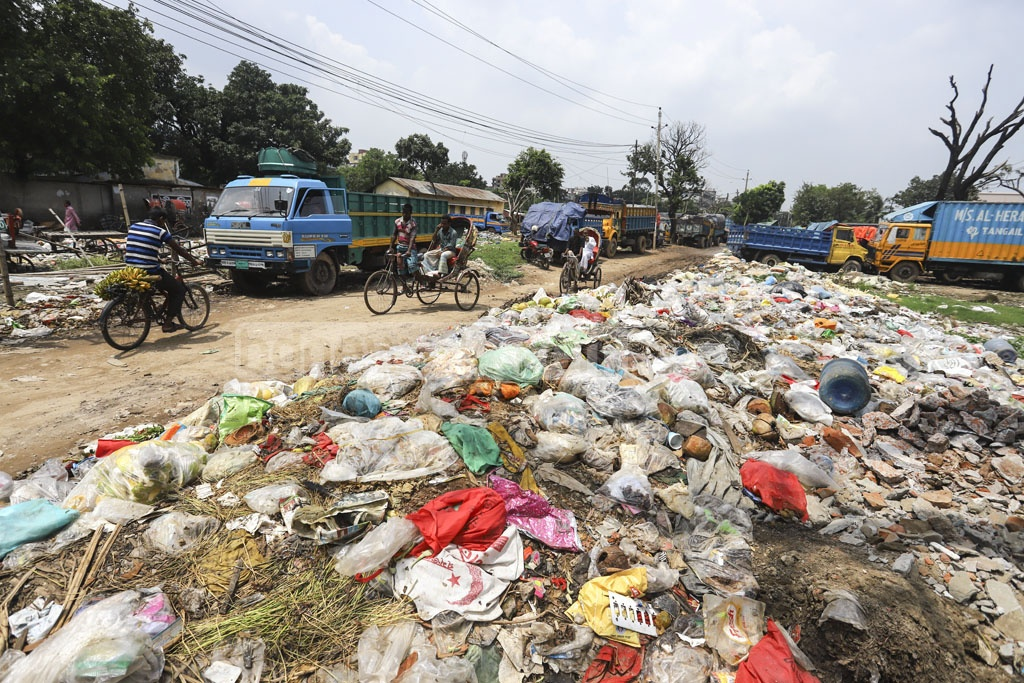 Pungent smell from garbage dumped on a field near Tejgaon Railway Station forces the people taking the street next to it to cover their nose. This photo was clicked on Thursday. Photo: Asif Mahmud Ove