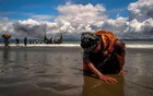 An exhausted Rohingya refugee woman touches the shore after crossing the Bangladesh-Myanmar border by boat through the Bay of Bengal, in Shah Porir Dwip, Bangladesh Sep 11, 2017. REUTERS