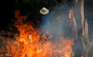 Amazon Fire 2 caption 2: FILE PHOTO: A man works in a burning tract of Amazon jungle as it is being cleared by loggers and farmers in Iranduba, Amazonas state, Brazil August 20, 2019. REUTERS