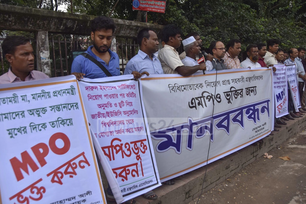 Assistant librarians demonstrate outside the National Press Club in Dhaka on Sunday demanding that the government include them in its monthly pay order or MPO scheme.