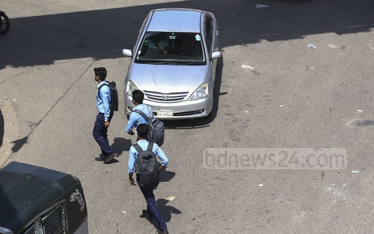 Students scamper across the busy Mirpur-10 intersection in Dhaka with vehicles whizzing by them. Photo: Mahmud Zaman Ovi