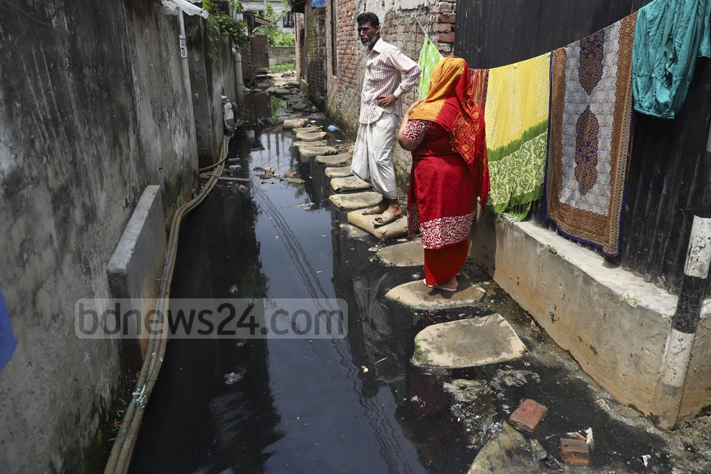 Residents of North Muradpur in Dhaka's Kadamtali have to wait when someone else comes from the opposite direction as they have to walk on a narrow path made of sandbags on waterlogged Haji Lal Mia Lane. Photo: Abdullah Al Momin