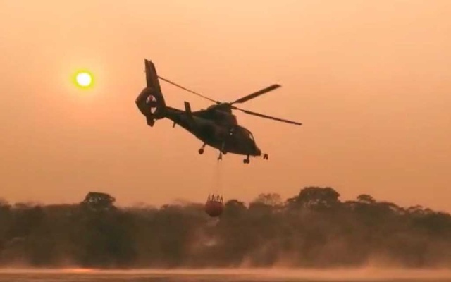 A Bolivian Air Force helicopter collects water to fight forest fire, near Robore, Bolivia Aug 19, 2019 in this still image taken from social media video. Jerjes Suarez Ruiz via REUTERS