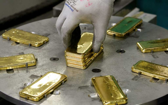 FILE PHOTO: An employee places bars of one kilogram fine gold on a machine before marking with a stamp at a plant of gold refiner and bar manufacturer Argor-Heraeus SA in the southern Swiss town of Mendrisio November 13, 2008. Reuters