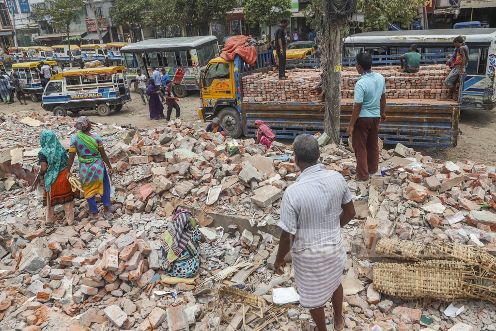 Shopkeepers taking away materials two days after hundreds of illegally constructed shops are demolished in an eviction drive along the railway tracks at Jurain in Dhaka. Photo: Abdullah Al Momin