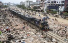 The Dhaka-Narayanganj train moving on the tracks in the capital's Jurain Railgate on Wednesday amid debris after hundreds of illegally built shops are demolished in an eviction drive. Photo: Abdullah Al Momin