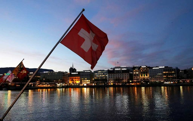 FILE PHOTO: A Swiss flag is pictured during the sunrise on the Commercial and Financial District in Geneva, Switzerland, November 23, 2017. Reuters