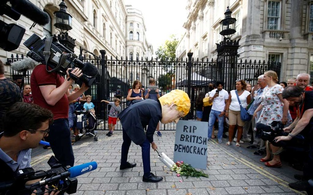 Anti-Brexit protestor: An anti-Brexit protestor holds a defaced placard of British Prime Minister Boris Johnson, outside Downing Street in London, Britain Aug 28, 2019. REUTERS