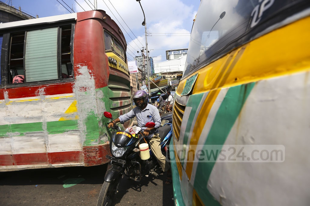 A motorcyclist sneaks through a narrow gap between two buses at the city's Paltan intersection on Thursday. Photo: Mahmud Zaman Ovi
