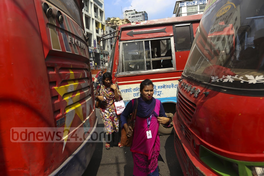 Women are also among those known as typical jaywalkers in Dhaka who sneak through narrow gaps between buses to cross street. This photo was taken at Paltan on Thursday. Photo: Mahmud Zaman Ovi