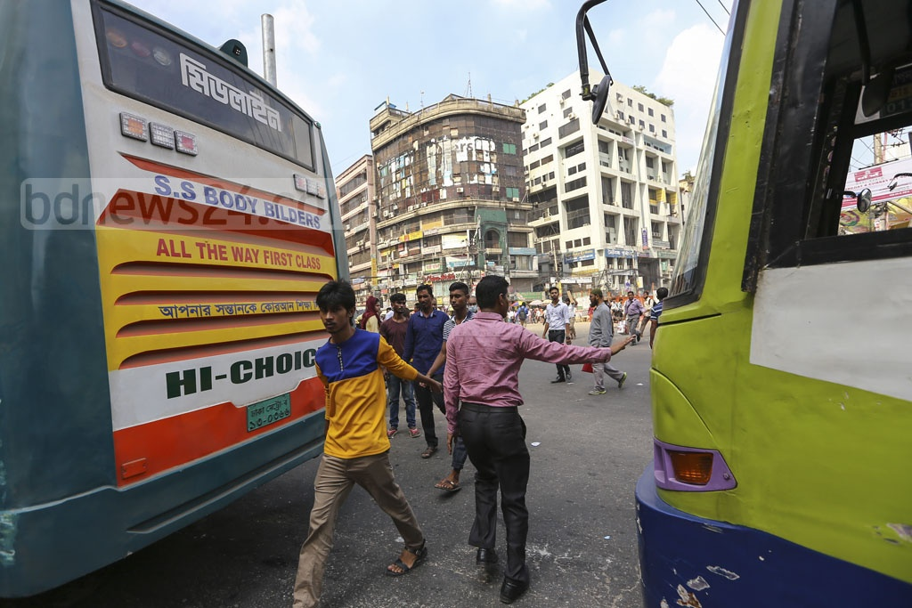 Pedestrians cross the street at the city's Paltan intersection through narrow gaps between buses on Thursday. Photo: Mahmud Zaman Ovi