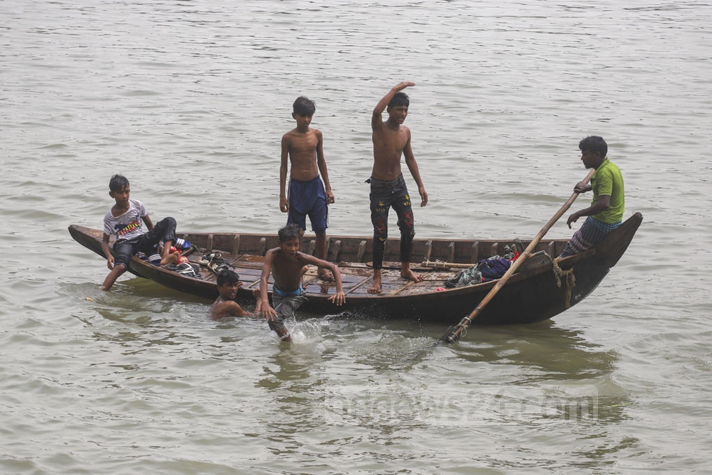 Boys from faraway areas take a boat ride in the Buriganga river to Kamrangirchar in Dhaka on Friday to play in the water which is relatively clean after monsoon rains. Photo: Abdullah Al Momin