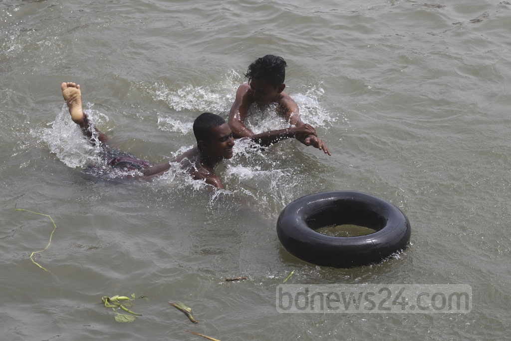 Children using tyres, cork sheets and everything they can to float while playing in the Buriganga river at Kamrangirchar in Dhaka on Friday. Photo: Abdullah Al Momin