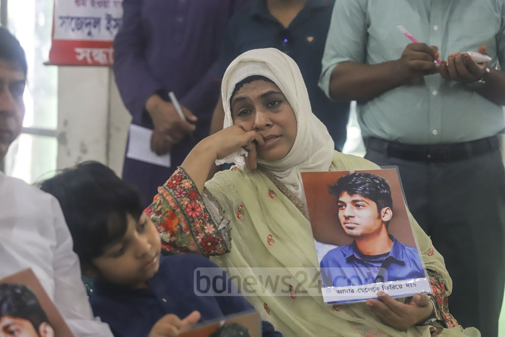 The mother of Ishraq Ahmed, a Bangladeshi student of McGill University in Canada who went missing from Dhaka's Dhanmondi on Aug 26 in 2017, cries as she holds a photo of her son at a discussion in the National Press Club in Dhaka on Friday marking the International Day of the Victims of Enforced Disappearances. Photo: Asif Mahmud Ove