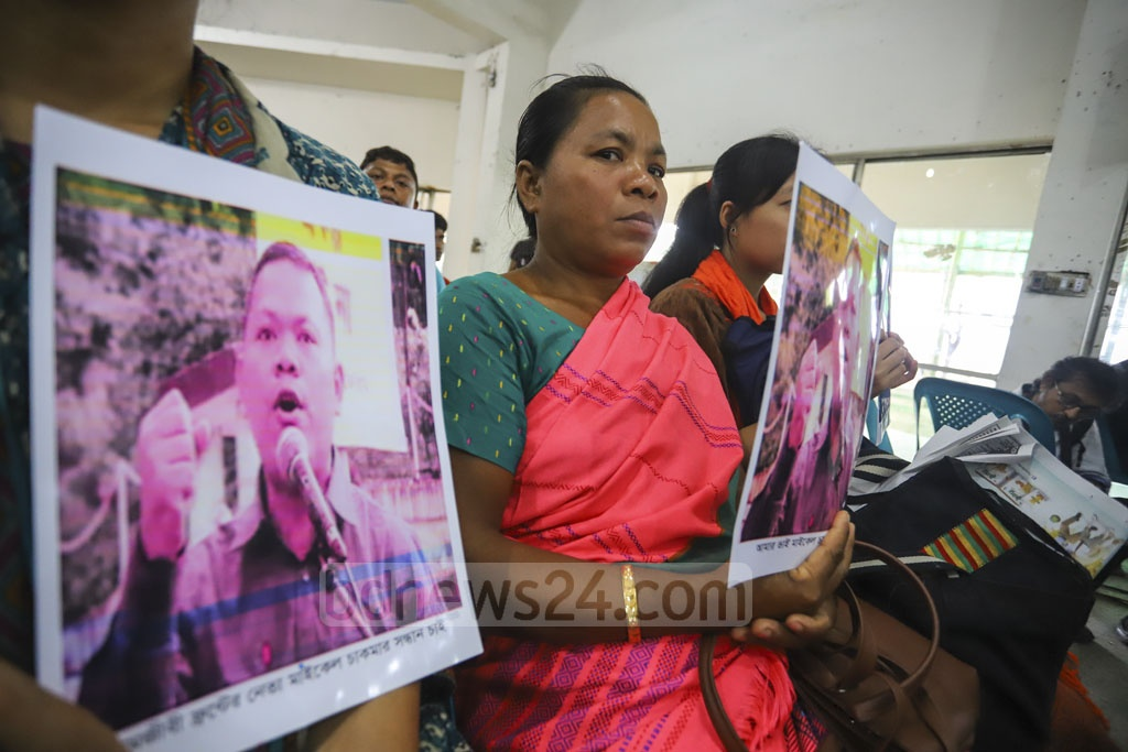 Subhadra Chakma holds a photo of his brother Michael Chakma, an alleged victim of forced disappearance, at a discussion in the National Press Club in Dhaka on Friday marking the International Day of the Victims of Enforced Disappearances. Photo: Asif Mahmud Ove