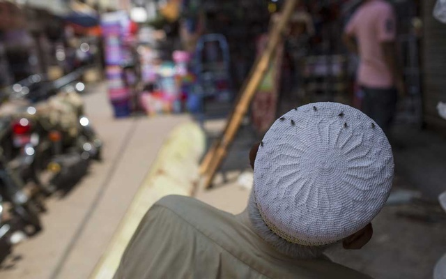 Flies coat a man's hat in the Bohri Bazaar in Karachi, Pakistan, Aug. 28, 2019. Pakistan's biggest city had heavy rains, bad drainage and a garbage problem — and now, bugs are everywhere. (Mustafa Hussain/The New York Times)