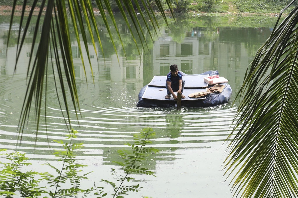 A boy crosses the Banani Lake in Dhaka by an improvised raft on Saturday. Photo: Asif Mahmud Ove