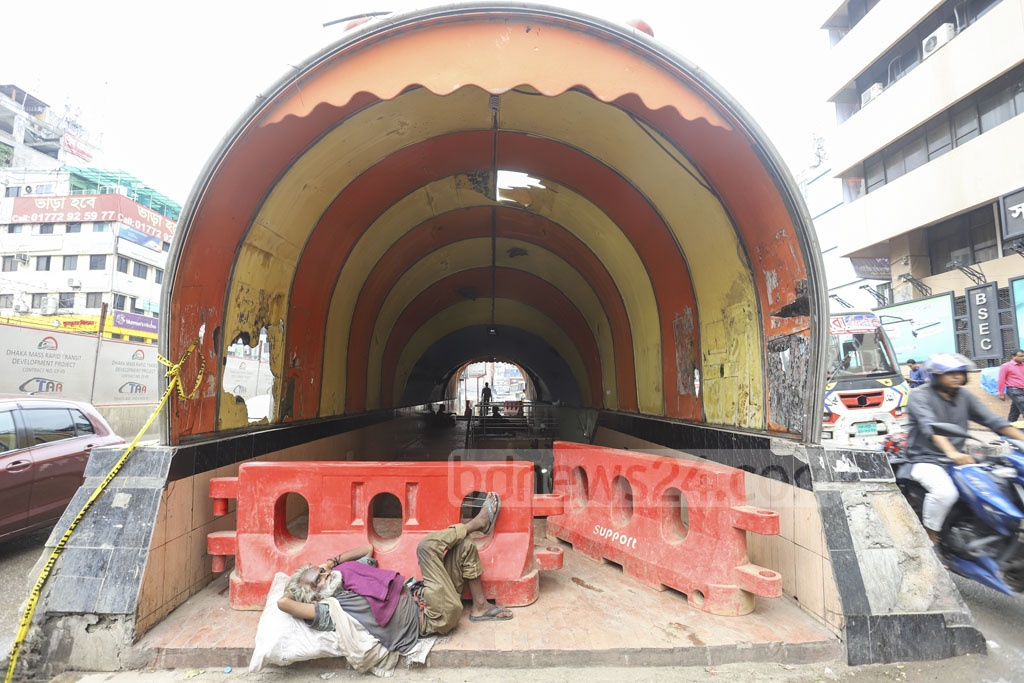 A homeless man rests on the partially blocked entrance of the 'Projapoti Guha' or Butterfly Cave underpass at Karwan Bazar in Dhaka on Saturday as people continue using it even after the authorities have declared it closed. Photo: Asif Mahmud Ove