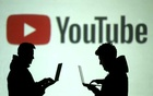FILE PHOTO: Silhouettes of mobile device users are seen next to a screen projection of Youtube logo in this picture illustration taken Mar 28, 2018. REUTERS