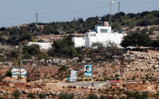 FILE PHOTO: A banner depicting Hezbollah leader Sayyed Hassan Nasrallah and an United Nation's post are seen in Lebanon from the Israeli side of the border, near Zar'it in northern Israel Aug 28, 2019. REUTERS