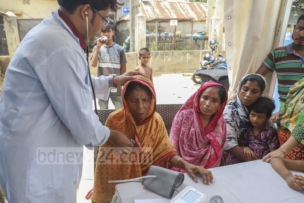 A physician checks a patient's condition during a healthcare campaign at Korail slum in the capital's Mohakhali area on Sunday. Photo: Abdullah Al Momin