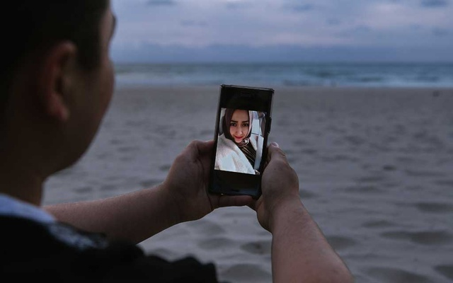 Almas Nizamidin, with a picture of his wife, his high school sweetheart, at Glenelg Beach outside Adelaide, Australia, Jan 30, 2018. His wife, Buzainafu Abudourexiti, was sentenced to seven years in prison in Xinjiang in 2017 for what Nizamidin calls trumped-up offences. The New York Times