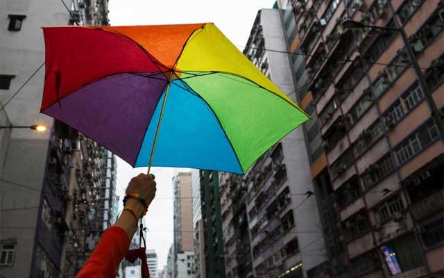 A participant holds a rainbow umbrella as he attends a lesbian, gay, bisexual and transgender (LGBT) Pride Parade in Hong Kong Nov 8, 2014. REUTERS
