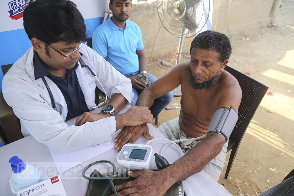 A doctor checks on a patient's condition during a healthcare campaign at the Korail slum in Mohakhali on Tuesday. Telenor Group launched a three-day campaign on Sunday. Photo: Mahmud Zaman Ovi