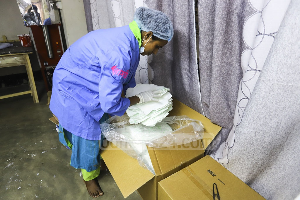A volunteer handles raw materials of the sanitary napkins imported from China. Photo: Asif Mahmud Ove