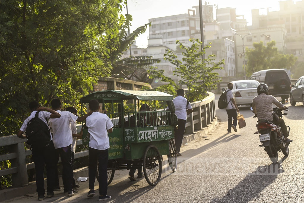 Boys pushing a school van on the U-loop in Dhaka's Rampura to help the puller on Wednesday. Photo: Mahmud Zaman Ovi