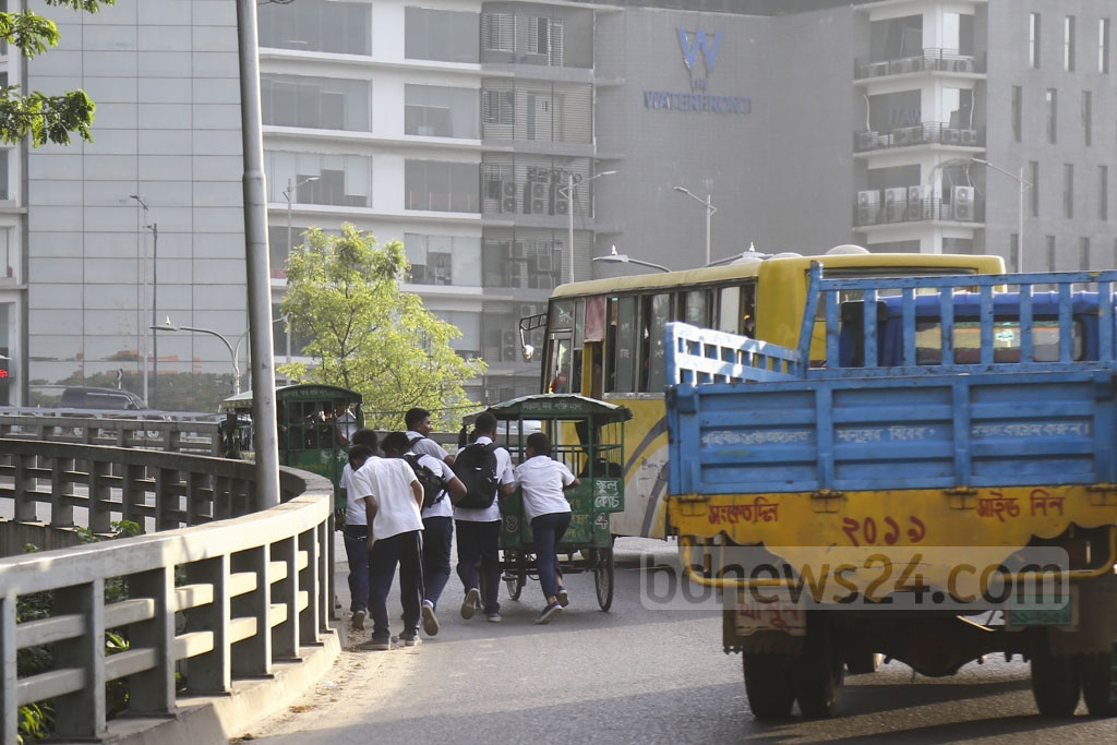The U-loop in Dhaka's Rampura is out of bounds for vehicles pulled by humans, but school van pullers breach the rule every day. This photo of a man pulling a school van while the boys are pushing it to help him was clicked on Wednesday. Photo: Mahmud Zaman Ovi