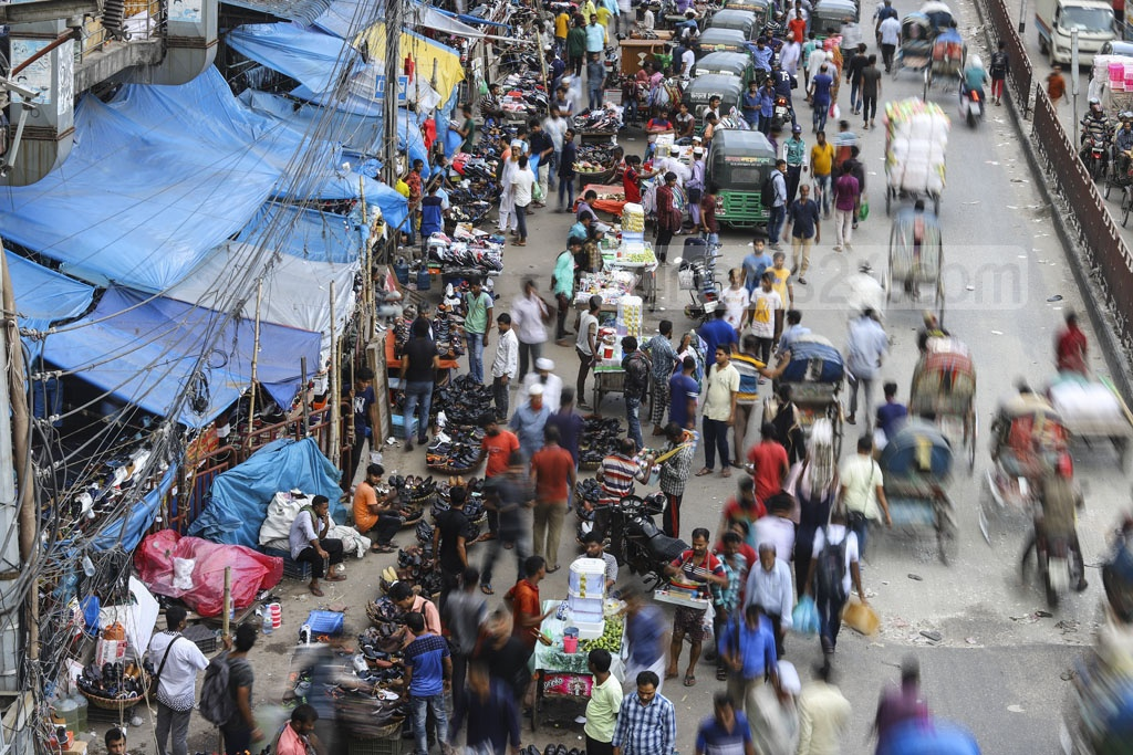 Hawkers are doing business illegally occupying the pavements and roads, bringing sufferings to the pedestrians. Photo: Asif Mahmud Ove