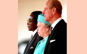 FILE PHOTO: Queen Elizabeth II and the Duke of Edinburgh stand with the President of Zimbabwe, Robert Mugabe (L), shortly before he reviewed a guard of honour in London May 17, 1994. REUTERS