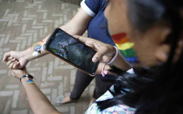 Two students take a photo of their painted wrists at a fest celebrating the first anniversary of a historic judgment that decriminalised gay sex in New Delhi, India on Sep 6, 2019. Thomson Reuters Foundation
