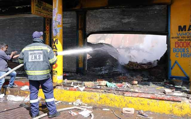 FILE PHOTO: A shop keeper watches as a fireman douses down a burned and damaged property after overnight unrest and looting in Alexandra township, Johannesburg, South Africa, September 3, 2019. REUTERS