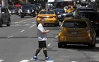 A pedestrian uses a phone while he crosses an intersection in New York on Jun 4, 2019. There's little concrete evidence to connect distracted walking to pedestrian deaths, according to a new report released by the city's Transportation Department. The New York Times