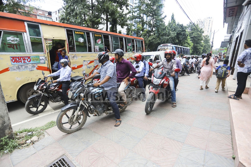 Motorcyclists ply a footpath in the capital's Gulshan-1 on Sunday despite police cracking down on the practice. Photo: Asif Mahmud Ove